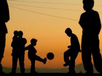 Young Peruvian boys play soccer near sunset in Arequipa, Peru July 9, 2004.  REUTERS/Carlos Barria