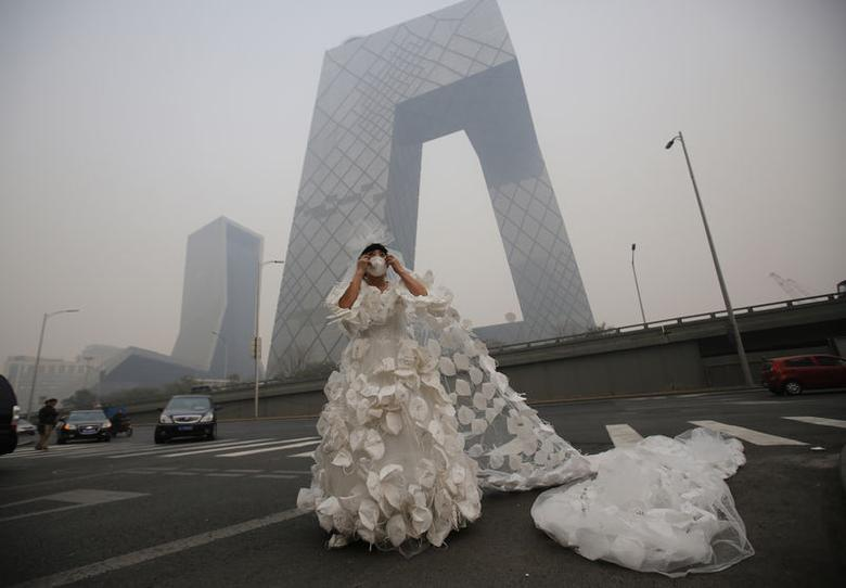 Kong Ning wears a wedding dress decorated with 999 face masks for her performance art work 'Marry the blue sky' as she poses for a photograph in front of the China Central Television (CCTV) Headquarters on a hazy day in Beijing November 19, 2014. REUTERS/Kim Kyung-Hoon/Files