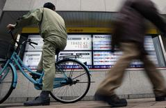 A man riding on a bicycle looks at an electronic board showing the Japan's Nikkei average outside a brokerage in Tokyo February 24, 2015. REUTERS/Yuya Shino