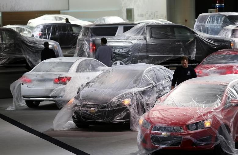 Vehicles are covered with protective wrap as workers prepare the General Motors automakers display ahead of the media preview of the North American International Auto Show at Cobo Center in Detroit, Michigan January 11, 2014.  REUTERS/Rebecca Cook