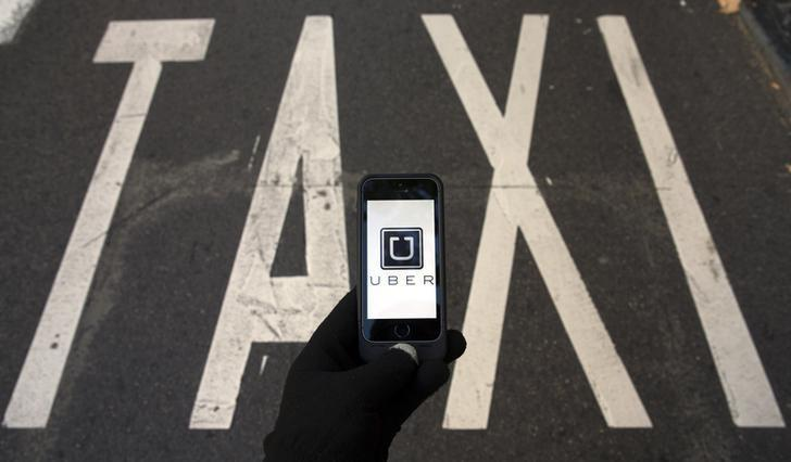 The logo of car-sharing service app Uber on a smartphone over a reserved lane for taxis in a street is seen in this photo illustration taken in Madrid on December 10, 2014. REUTERS/Sergio Perez/Files