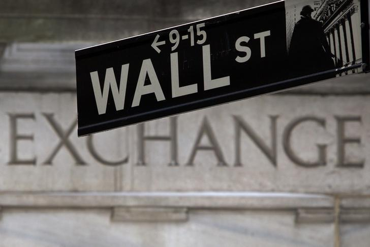 A Wall Street sign is pictured in front of the New York Stock Exchange, open during Winter Storm Juno, in the Manhattan borough of New York January 27, 2015.   REUTERS/Carlo Allegri/Files