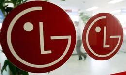 An employee of LG Electronics walks behind company logos at a branch in Seoul February 21, 2005. REUTERS/You Sung-Ho