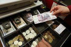 Кассир держит в руках рублевую купюру в магазине в Красноярске 2 февраля 2015 года. Рубль подорожал в четверг за счет роста цен на нефть, а также благодаря продажам валюты как от экспортеров, так и от крупных игроков, оценивающих сейчас рубль лучше аналогов при одновременно невысоком корпоративном валютном спросе. REUTERS/Ilya Naymushin