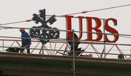 Workers are seen beside a logo of Swiss bank UBS in Zurich February 13, 2015.  REUTERS/Arnd Wiegmann