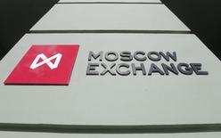 Логотип у входа в офис Московской биржи 14 марта 2014 года. Российские фондовые индексы слегка снижаются в ходе пятничных торгов, а бумаги ВТБ, сообщившего об убытке в 2014 году, не выделяются на общем фоне. REUTERS/Maxim Shemetov
