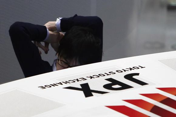 An employee of the Tokyo Stock Exchange (TSE) stretches his body as he works at the bourse at TSE in Tokyo March 13, 2015. REUTERS/Yuya Shino