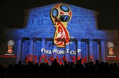 Journalists look at a light installation showing the official logotype of the 2018 FIFA World Cup during its unveiling ceremony at the Bolshoi Theater building in Moscow, October 28, 2014. REUTERS/Maxim Shemetov
