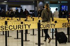 Passengers make their way in a security checkpoint at the International JFK airport in New York October 11, 2014. REUTERS/Eduardo Munoz