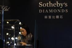 En la imagen, una trabajadora de Sotheby's durante una exhibición de diamantes previa a una subasta en Pekín, el 28 de noviembre de 2013. Sotheby's contará con una otra vía donde poder luchar por sus codiciados artículos, al lanzar junto a eBay una nueva plataforma que permitirá emitir en directo las ventas de la casa de subastas en Nueva York a partir del próximo mes. REUTERS/Kim Kyung-Hoon