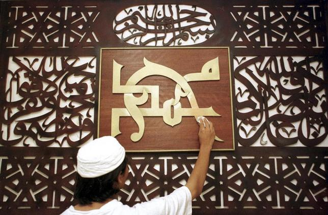 A worker cleans an Islamic plaque of calligraphy saying ''Mohammad'' on the morning of Eid al-Fitr in a mosque in Kota Bharu, in Malaysia's northeastern state of Kelantan in this January 8, 2000 file photo. REUTERS/Staff/Files