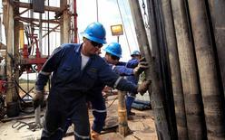 Empleados de Pacific Rubiales trabajando junto a una tubería de excavación en el Campo Rubiales en Meta, Colombia, ene 23 2013. Una alarmante caída de la actividad de exploración y de las inversiones para el desarrollo de pozos amenaza con impedir que la producción colombiana de petróleo supere el millón de barriles diarios en el 2015 y empiece una caída sostenida en los próximos años, advirtió el miércoles el gremio del sector.  REUTERS/Jose Miguel Gomez