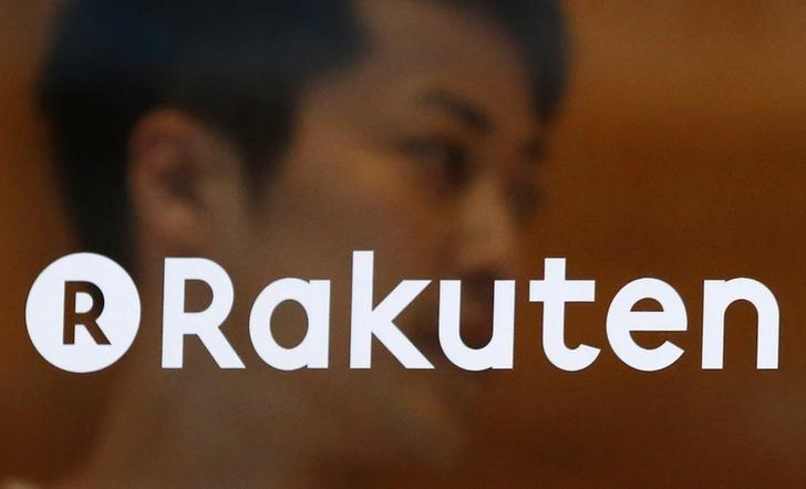 A staff of Rakuten Cafe is seen behind a logo of Rakuten Inc. at a shopping district in Tokyo August 4, 2014.  REUTERS/Yuya Shino