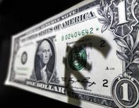 Символ евро на купюре 1 доллар США. Мадрид, 10 марта 2015 года. Доллар в четверг отвоевал позиции после резкого падения в среду, вызванного намного более осторожным заявлением ФРС о ключевой ставке, чем ожидалось. REUTERS/Sergio Perez
