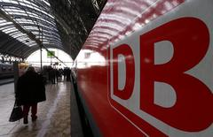 A woman walks past a train of Deutsche Bahn railway operator at the main train station in Frankfurt November 21, 2014. REUTERS/Ralph Orlowski