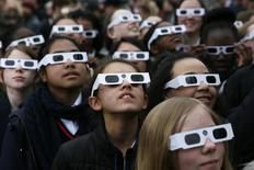 School children wearing protective glasses pose for photographers outside The Royal Observatory during a partial solar eclipse in Greenwich, south east London March 20, 2015. REUTERS/Stefan Wermuth