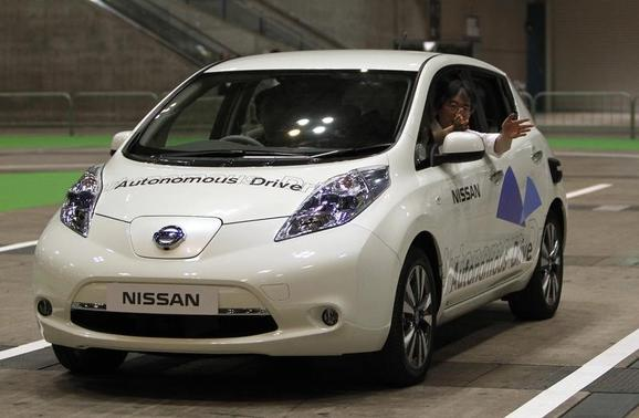 A staff member of Nissan gestures to the media as he rides its LEAF electronic car with the new driving system 'Autonomous Drive', which utilizes sensors and cameras to drive automatically, during a photo opportunity at CEATEC (Combined Exhibition of Advanced Technologies) JAPAN 2013 in Chiba, east of Tokyo, October 1, 2013. REUTERS-Yuya Shino