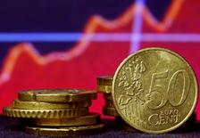Монеты евро на фоне рыночного графика. Зеница, 13 марта 2015 года. Евро поднялся до $1,10 в среду и подорожал к большинству основных валют благодаря хорошим показателям делового климата в Германии, ставшим еще одним доказательством того, что экономика еврозоны укрепляется. REUTERS/Dado Ruvic