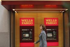 A woman walks past teller machines at a Wells Fargo bank in San Francisco, California October 10, 2013.  REUTERS/Robert Galbraith