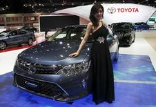 A model poses beside a Toyota Camry Hybrid during a media presentation of the 36th Bangkok International Motor Show in Bangkok March 24, 2015. REUTERS/Chaiwat Subprasom