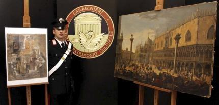 A Carabinieri paramilitary policeman stands next to a painting of Luca Carlevarijs (R) and ''Violin e bouteille de bass'' painting of Pablo Picasso during a news conference in Rome, in this March 27, 2015 handout picture provided by Carabineri Press Office.  REUTERS/Carabinieri Press Office/Handout via Reuters