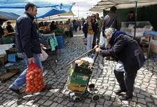 En la imagen, una mujer empuja una carretilla en el mercado de  Malveira, 30 kilómetros al norte de Lisboa. 28 de marzo, 2013. La confianza en la economía de la zona euro creció en marzo por cuarto mes consecutivo y alcanzó su mayor nivel desde julio del 2011, mostró el lunes un informe de la Comisión Europea, lo que sugiere que la debilidad del euro y precios del petróleo más bajos están impulsando la recuperación.  REUTERS/Jose Manuel Ribeiro