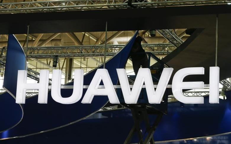 A worker adjusts the logo at the stand of Huawei at the CeBIT trade fair in Hanover March 15, 2015.  REUTERS/Morris Mac Matzen