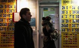 Прохожие у пункта обмена валюты в Киеве. 26 февраля 2015 года. Комитет по монетарной политике Национального банка Украины предложил оставить ключевую ставку рефинансирования - дисконтную - на уровне 30 процентов из-за сохраняющихся рисков дестабилизации денежно-кредитного рынка, высоких инфляционных и девальвационных ожиданий, говорится в сообщении НБУ. REUTERS/Valentyn Ogirenko