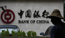 Мужчина у отделения Bank of China в Пекине. 14 июля 2014 года. Китай введет в действие схему страхования для банковских депозитов с 1 мая, сообщило правительство во вторник, реализуя реформу, которая считается жизненно важной для либерализации банковского сектора. REUTERS/Kim Kyung-Hoon