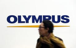 A man passes a logo of Olympus Corp outside the company's showroom in Tokyo December 21, 2012. REUTERS/Yuriko Nakao