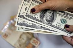 Mulher segura notas de dólar, enquanto notas de reais são vistas sobre a mesa, no Rio de Janeiro. 31/03/2015 REUTERS/Sergio Moraes