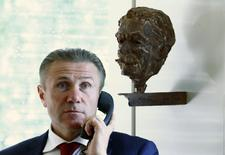 International Olympic Committee (IOC) member Sergei Bubka speaks on the phone in front of a statue of Baron Pierre de Coubertin at the start of the Executive Board meeting at the IOC headquarters in Lausanne July 7, 2014.  REUTERS/Denis Balibouse