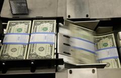 Billetes de un dólar en su proceso de empaquetamiento en la Casa de la Moneda en Washington, nov 14 2014. El dólar se depreciaba con fuerza y los precios de los bonos del Tesoro estadounidense escalaban el viernes, tras divulgarse un informe de empleo significativamente débil, que aumentó la expectativa de que la Reserva Federal mantenga por más tiempo su política monetaria expansiva.   REUTERS/Gary Cameron