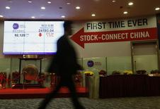"A man walks past a panel displaying the closing blue chip Hang Seng Index and a banner on ""Shanghai-Hong Kong Stock Connect"" inside the Hong Kong Exchange in Hong Kong March 5, 2015. H REUTERS/Bobby Yip"