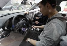 A man sits in a newly bought BMW X3 car at a dealership in central Beijing May 4, 2011.  REUTERS/Jason Lee
