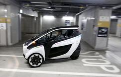 A Toyota i-Road electric vehicle drives in a underground parking lot in Tokyo, April 9, 2015. REUTERS/Thomas Peter