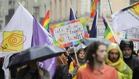People hold placards and rainbow-colored flags as they attend the Baltic Pride event in Riga, June 2, 2012. REUTERS/Ints Kalnins