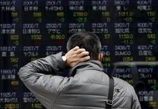 Прохожий у брокерской конторы в Токио. 10 апреля 2015 года. Азиатские фондовые рынки завершили неделю ростом, причем рынки Японии и Китая достигли многолетних максимумов. REUTERS/Yuya Shino
