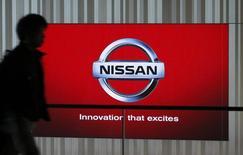 A man walks past a screen displaying the brand logo of car maker Nissan at a showroom in Yokohama, south of Tokyo, December 18, 2014. REUTERS/Thomas Peter