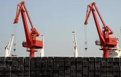 Piles of steel pipes to be exported are seen in front of cranes at a port in Lianyungang, Jiangsu province March 7, 2015. REUTERS/Stringer/Files