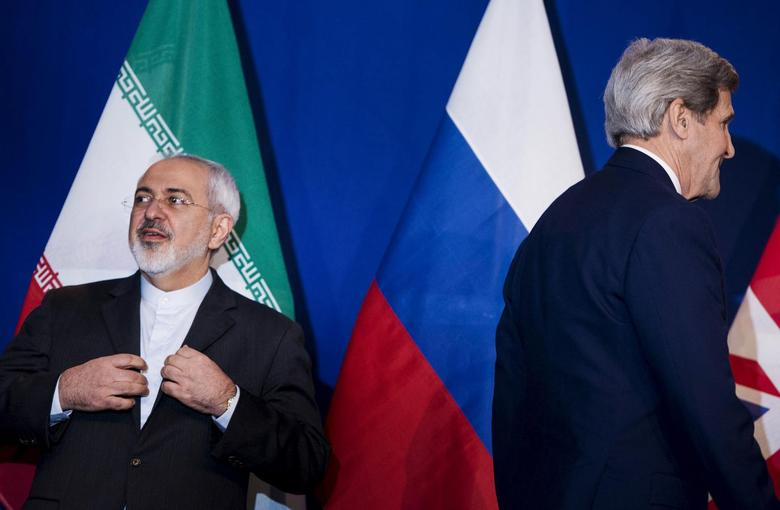 Iranian Foreign Minister Javad Zarif (L) waits to make a statement next to U.S. Secretary of State John Kerry (R), following nuclear talks at the Swiss Federal Institute of Technology in Lausanne (Ecole Polytechnique Federale De Lausanne) April 2, 2015.  REUTERS/Brendan Smialowski