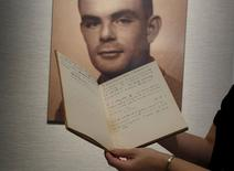 A notebook of British mathematician and pioneer in computer science Alan Turing is displayed in front of a photo of him during an auction preview in Hong Kong March 19, 2015.  REUTERS/Bobby Yip