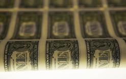 Una lámina de billetes de dólar durante su proceso de producción en Washington. Imagen de archivo, 14 noviembre, 2014.  El dólar subió el lunes frente al euro debido a que continuaron las apuestas de la semana pasada de que la Reserva Federal de Estados Unidos subirá sus tasas de interés en los próximos meses, mientras que el yen se apreció levemente por comentarios de un asesor económico de alto perfil.  REUTERS/Gary Cameron