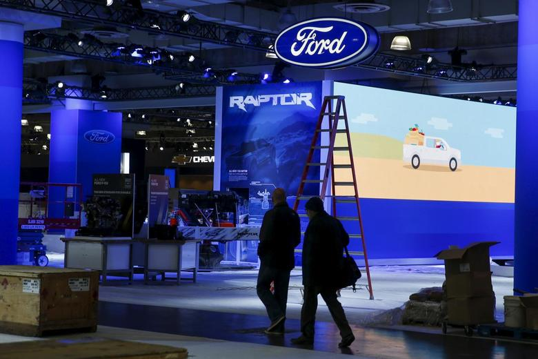 People walk near the Ford exhibit area of the New York International Auto Show at the Javits Center ahead of the event in New York March 30, 2015.REUTERS/Shannon Stapleton