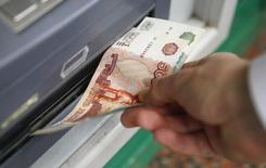 Мужчина забирает деньги из банкомата. 2 сентября 2014 года. Рубль подорожал утром среды в условиях восходящей динамики нефти и в стартовавший налоговый период, предполагающий рост продаж  экспортной выручки для расчетов с бюджетом. REUTERS/Maxim Zmeyev