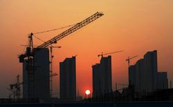 The sun sets behind a residential construction site in Rizhao, Shandong province April 14, 2015.  REUTERS/Stringer