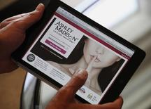 Ashley Madison founder Noel Biderman demonstrates his website on a tablet computer during an interview in Hong Kong, August 28, 2013. REUTERS/Bobby Yip