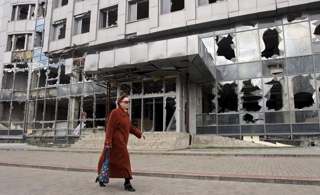 A woman walks past a building damaged by fighting in Donetsk, April 15, 2015.   REUTERS/Igor Tkachenko