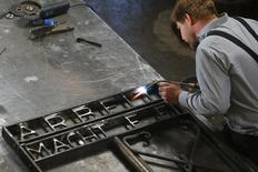 "Blacksmith Michael Poitner makes a replica of the main gate of the former concentration camp in Dachau with the Nazi slogan ""Arbeit macht frei"" (Work sets you free) in his workshop in Biberbach near Dachau April 15, 2015. REUTERS/Michael Dalder"