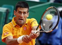 Novak Djokovic of Serbia returns the ball to Marin Cilic of Croatia during their quarter-final match at the Monte Carlo Masters in Monaco April 17, 2015.  REUTERS/Eric Gaillard